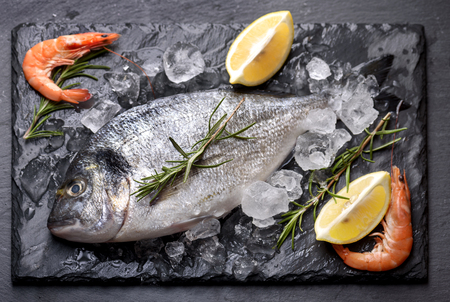 gilthead: Seafood cooking preparation.Top view of dorado and shrimps with herbs and lemon on black slate.