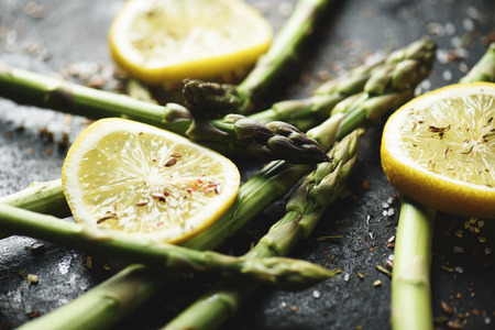 vegetarian cuisine: Vegetarian cuisine recipe. Fresh asparagus with lemon and spices on black plate closeup.