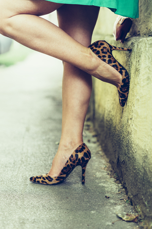 Sexy female legs closeup. Woman on the street in leopard pattern print high heeled shoes.