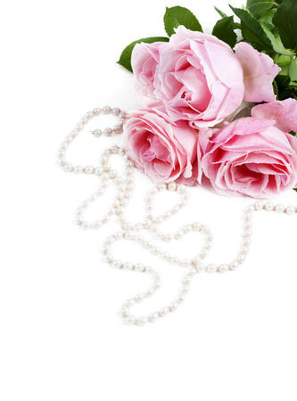 Beautiful pink roses and necklace pearls isolated over white background. Flower bouquet and jewelry for wedding or valentine decoration.