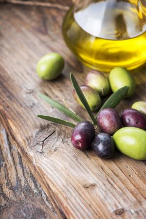 aceite de oliva: aceitunas frescas y una botella de aceite de oliva virgen extra a bordo textura de madera.