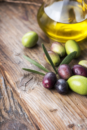 Fresh olives and extra virgin olive oil bottle on wooden textured board.