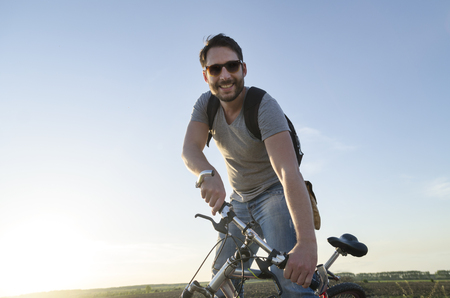 adventure holiday: Man riding a bicycle and having outdoor fun. Summer holiday backpack adventure traveler. Stock Photo