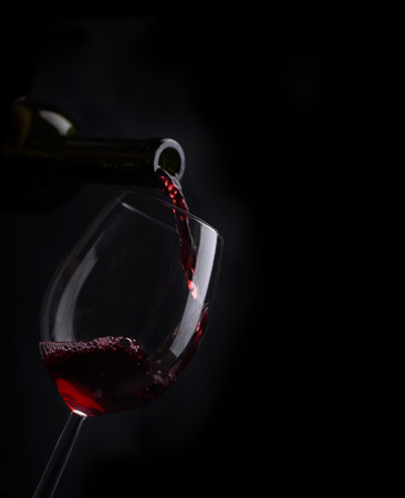beverage menu: Red wine pouring in wineglass from bottle over black background. Wine list design menu with copyspace. Alcohol beverage card backdrop. Stock Photo