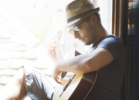 Portrait of young stylish guy with hat and sunglasses plays guitar at home. Creative man have leisure time with music at summer holiday. Hipster lifestyle concept. 版權商用圖片