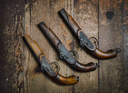 Two vintage pistols on wooden background