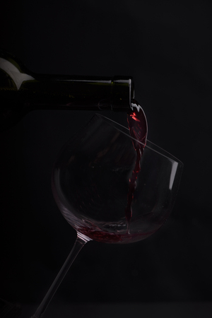 cabarnet: Red wine pouring in wineglass from bottle over black background. Wine list design menu with copyspace. Alcohol beverage card backdrop. Stock Photo