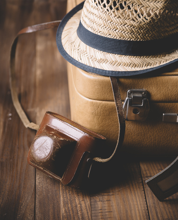 adventure holiday: Vintage case, hipster hat,  and retro camera on wooden background still life.. Summer holiday vacation and adventure traveling concept.