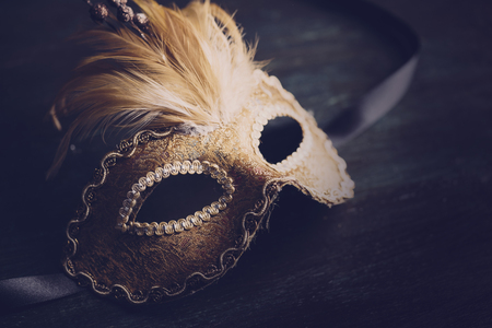 Golden venetian ball mask over dark background with copyspace. Masquerade party or holiday event celebration concept. Imagens