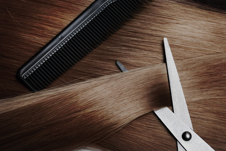 Healthy long brown dyed hair lock extensions and professional hairdresser scissors and comb. Hairstyle and hair treatment salon accessories.