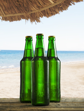 Refreshing cold beer bottles on beach bar table with water drops. Summer cocktail drink party on tropical island. Stock Photo
