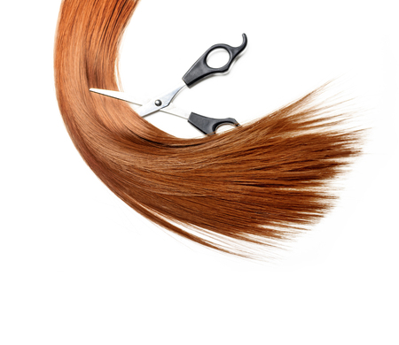 Healthy long red dyed hair lock extensions cutting with professional hairdresser scissors isolated over white background. Hair wig and hairdressing accessories with copyspace.  Hairstyle salon object.