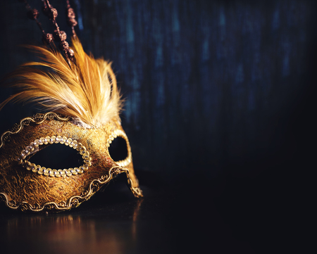 Golden venetian ball mask over dark background with copyspace. Masquerade party or holiday event celebration concept. Archivio Fotografico