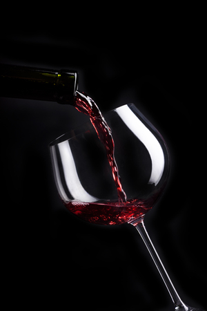 Red wine pouring in wineglass from bottle over black background. Wine list design menu with copyspace. Alcohol beverage card backdrop. Фото со стока