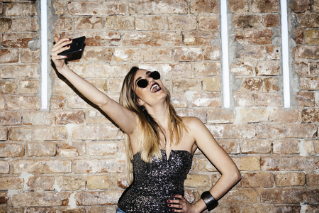 Young sexy woman posing in nightclub and taking selfie with her smartphone. Glamour stylish beautiful girl having fun in front of disco brick wall