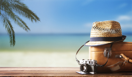 Vintage suitcase, hipster hat, photo camera and passport on wooden dack. Tropical sea, beach and palm three in background. Summer holiday traveling concept design banner with copyspace.