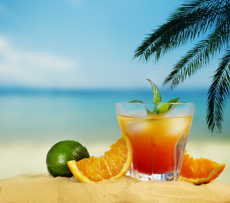 Orange cocktail and citrus fruit on tropical sandy beach. Summer holiday and beach party design. Stock Photo