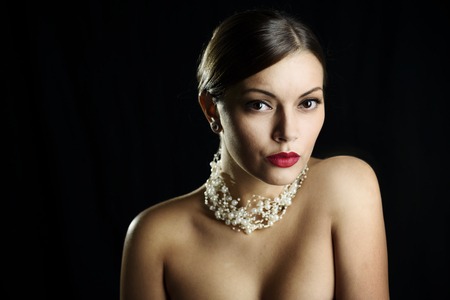 Beautiful young lady with elegant event makeup and jewelry pearls over black background. Glamour portrait of sensual woman with red lipstick and luxury evening accessories. Female fashion and beauty.