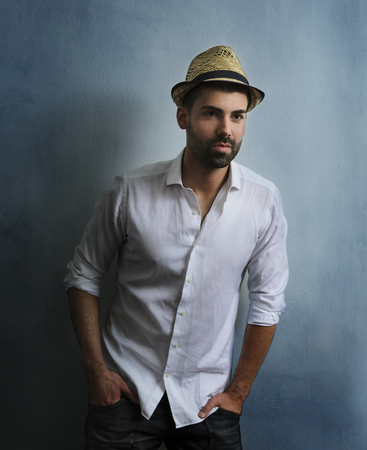 Young sexy hipster guy with beard posing in front of blue grunge wall. Portrait of stylish male model with retro hat and casual style clothing. Mans fashion and beauty.