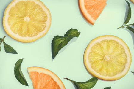 Citrus slices and mint herbs pattern on retro mint background from above. Top view of orange and lemon fruit slices on pastel background.
