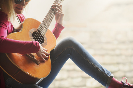 Closeup of young happy hipster woman plays the guitar with copyspace background. Summer fun and youth lifestyle concept.