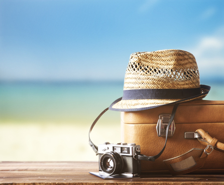 Vintage suitcase, hipster hat, photo camera and passport on wooden deck. Tropical sea and sandy beach a in background. Summer holiday traveling design concept.