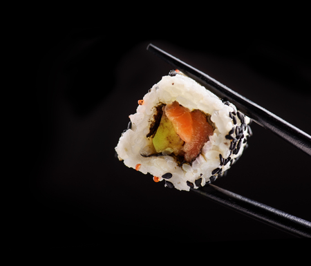 Closeup of traditional japanese sushi roll with salmon and tuna fish on bamboo chop sticks over black background. Sushi bar menu design with copyspace. Фото со стока