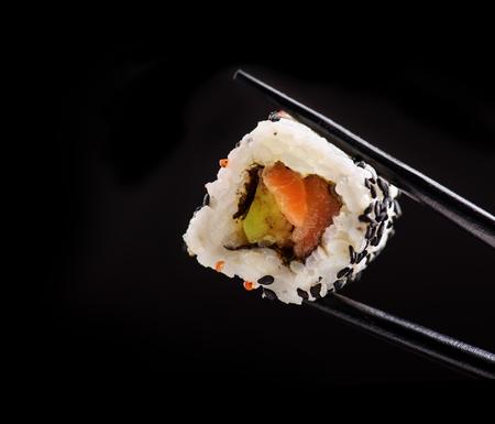 De close-up van traditioneel Japans sushi rolt met zalm en tonijnvissen op bamboekarbonade plakt over zwarte achtergrond. Het menuontwerp van de sushibar met copyspace.
