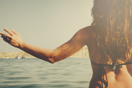 Young hipster girl from behind having fun in the sea. Summer holiday travel to tropical island. Фото со стока
