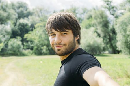 Portrait of young handsome man holding camera and taking outdoor selfie with smartphone. Guy enjoy nature, smiling and looking back in camera.