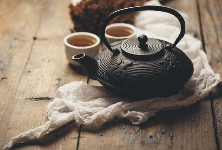 Still life with traditional asian herbal tea prepared in vintage cast iron teapot with organic dry herbs on rustic wooden table. Retro filter. Stock Photo