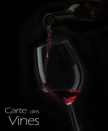 Vino rojo que vierte en copa de la botella sobre fondo negro. Menú de diseño de la carta de vinos con copyspace. Telón de fondo de la tarjeta de bebida de alcohol Foto de archivo - 81937252