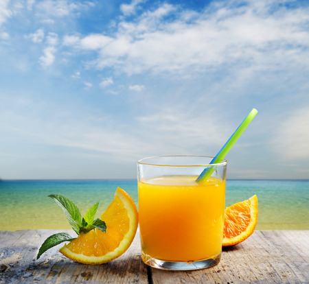 Orange juice vodka cocktail on tropical sandy beach. Summer holiday and beach party design. Stock Photo - 83884735