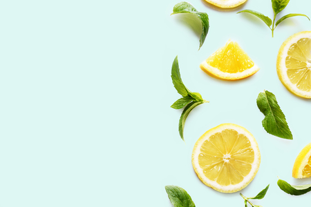 Top view of citrus slices and mint herbs frame on retro mint background with copyspace