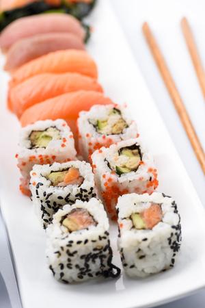Sushi met zalm en tonijnvissen met eetstokjes in witte plaat worden geplaatst die. Traditionele Japanse keuken. Stockfoto - 87520126