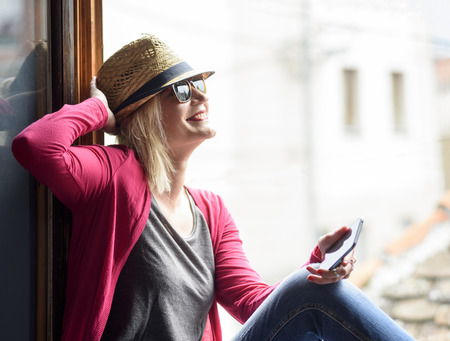 Young happy hipster woman with stylish hat, holding smartphone, laughing and enjoy the sun. Youth lifestyle concept.  Фото со стока