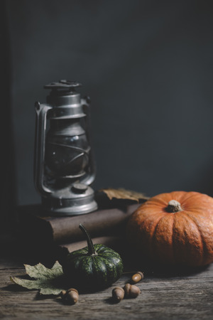 Still life with old lantern, halloween pumpkin and autumn decoration on rustic wooden table. Thanksgiving and Halloween holiday concept with copyspace.