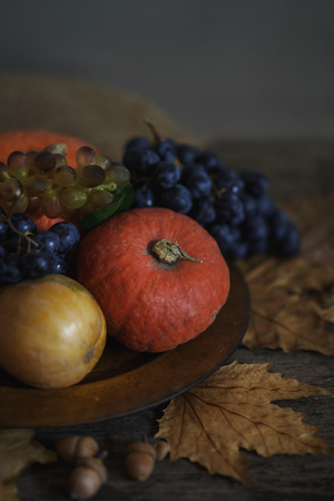 Happy thanksgiving holiday concept. Still life of autumn leaves, pumpkin, and fruits on rustic wooden table.