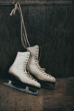 Seasonal winter holiday scene with pair of white ice skates on rustic wooden background with copyspace.