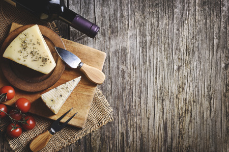 Top view of red wine and cheese on rustic wooden background with copyspace. French cuisine product.