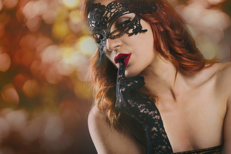 Closeup of sexy red haired woman with laced gloves and venetian mask in front of blur night lights. New year night and event party celebration. Luxury and glam lifestyle.