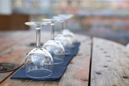 Empty wine glasses on rustic wooden table in retro restaurant interior. Фото со стока