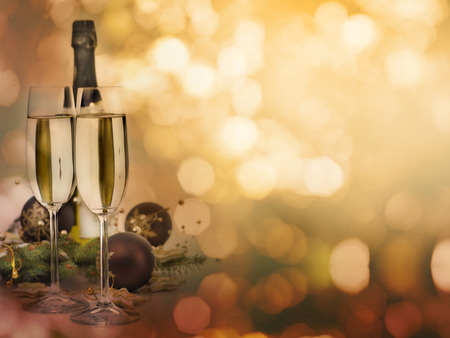 Two champagne glasses and christmas decoration with shiny bokeh lights background with copyspace. Christmas and New Year celebration party design.