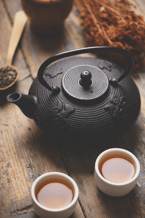 Still life with traditional asian herbal tea prepared in vintage cast iron teapot with organic dry herbs on rustic wooden table. Retro filter. Фото со стока