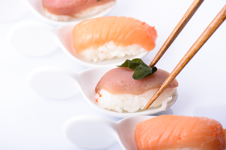 Closeup of traditional japanese sushi set with salmon and tuna fish isolated on white background. Sushi bar menu design. Фото со стока