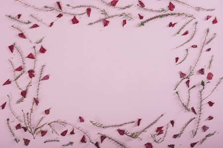 Floral pattern frame with flowers and petals over pink background. Flat lay border. Valentines day design from above.