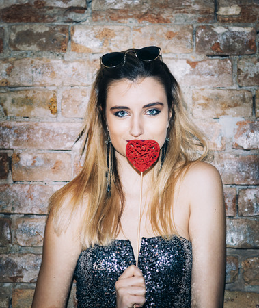 Beautiful stylish young woman holding valentine heart in in nightclub. Valentines day party. Фото со стока