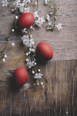 Red easter eggs and spring cherry blossom on rustic wooden table from above. Easter holiday greeting card.