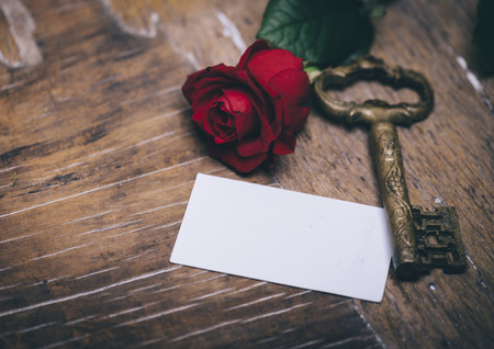 Valentines day still life concept. Valentine gift, red rose, vintage key and empty greeting card on wooden table. Valentine holiday design.
