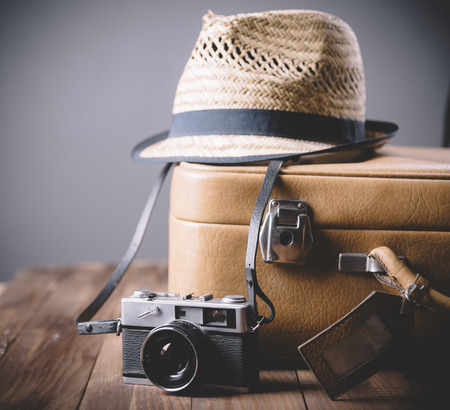 Vintage case, hipster hat, and retro camera on wooden background still life. Summer holiday vacation and adventure traveling concept with copyspace.